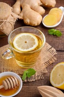 Gemberwortelthee met citroen en honing op houten tafel.