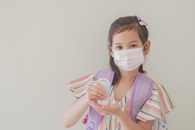 Gemengd aziatisch meisje dat masker draagt en handdesinfecterend middel, terug naar schoolconcept toepast