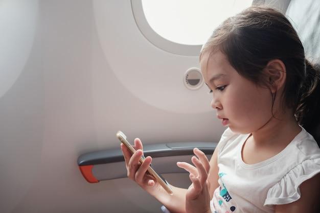 Gemengd aziatisch meisje met behulp van slimme telefoon tijdens de vlucht, familie reizen in het buitenland met kinderen