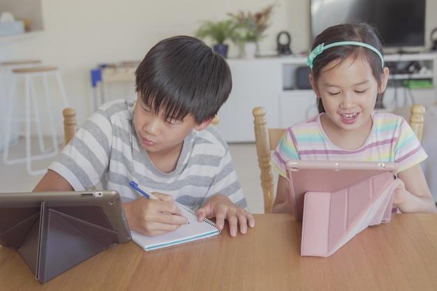 Gemengd aziatisch meisje thuis met behulp van digitale tablet, luisteren naar podcast, gaming, online onderwijs, e-learning, homeschooling, sociale afstand, isolatie, lockdown concept