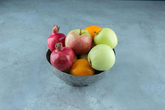 Gemengd fruit in een metalen kom op blauw.