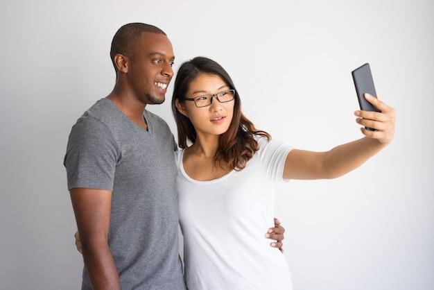 Gemengd gerend paar studenten die gemeenschappelijke selfie met telefoon nemen.