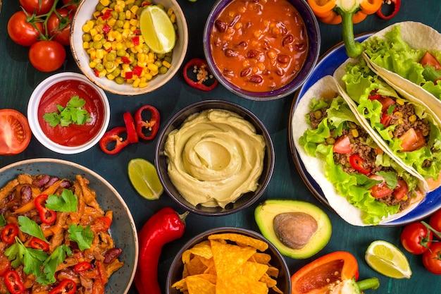 Gemengd mexicaans eten. feestvoedsel. guacamole, nacho's, fajita, vleestaco's, salsa, paprika's, tomaten op een houten tafel. bovenaanzicht.