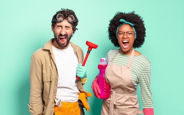 Gemengd paar dat agressief schreeuwt, ziet er erg boos uit, gefrustreerd, verontwaardigd of geërgerd, schreeuwend geen huishoudconcept huisreparatieconcept repairs