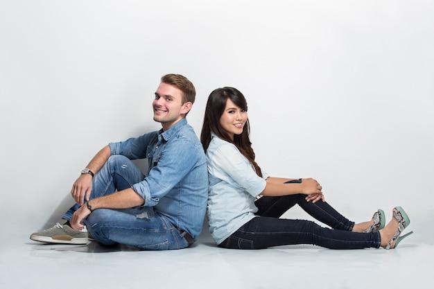 Gemengd paar zitten rug aan rug op de vloer