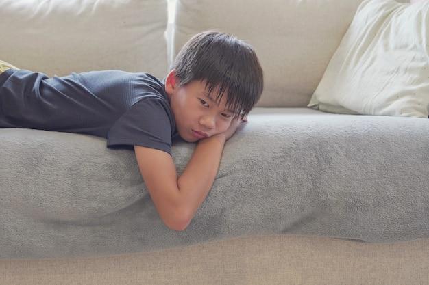 Gemengd ras aziatische preteen jongen verveeld liggend op de bank thuis, sociale afstand, quarantaine, isolatie concept, autisme bewustzijn, geestelijke gezondheid