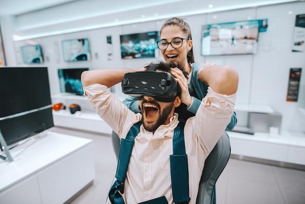 Gemengd ras bebaarde man probeert virtual reality-technologie terwijl vrouw kijkt naar wat hij doet.