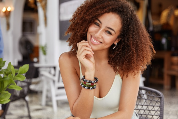 Gemengd ras donkere huid afro-amerikaanse vrouw met borstelige kapsel, draagt armband en casual t-shirt, in goed humeur, rust in cafetaria.