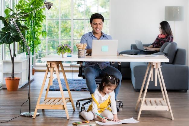 Gemengd ras familie deeltijd in de woonkamer. blanke vader die een notebookcomputer gebruikt om te werken en half thais speelt en schildert onder het bureau, terwijl een aziatische moeder met een laptop haar werk op de bank doet.