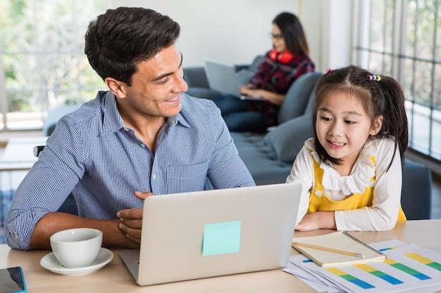 Gemengd ras familie die bij elkaar blijft, blanke vader zit en werkt aan een bureau en geeft les aan een kleine schattige dochter van een half ras, een witte aziatische moeder die een laptopcomputer op de bank gebruikt. idee voor thuiswerk.