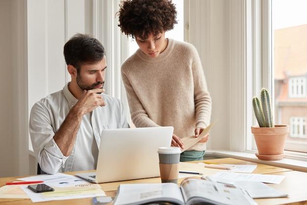 Gemengd ras familiepaar onderzoekt papierwerk, vraagt elkaar om advies, poseert tegen gezellig huiselijk interieur bij raam, gebruikt laptop, drinkt afhaalkoffie.