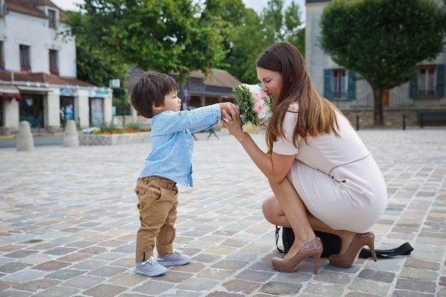 Gemengd ras jongen feliciteert zijn moeder en geeft haar bloemboeket