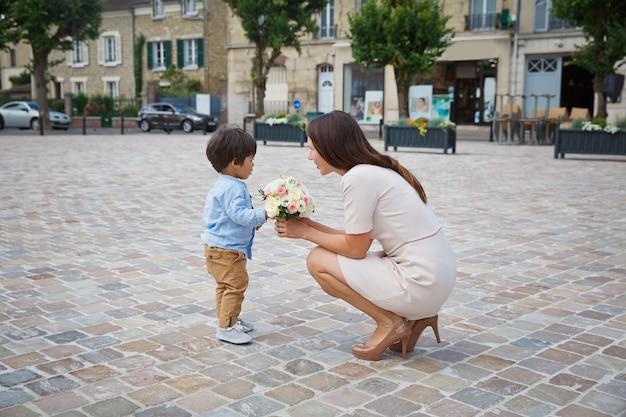 Gemengd ras jongen zoontje feliciteert zijn moeder en geeft haar bloemboeket, ze knuffelen en lachen samen. familie vakantie concept