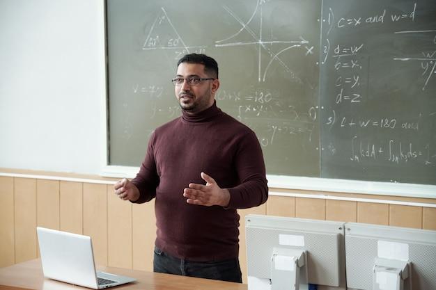 Gemengd ras man iets uit te leggen aan studenten door blackboard
