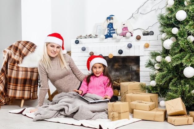 Gemengd ras moeder en dochter knuffelen in de buurt van de kerstboom