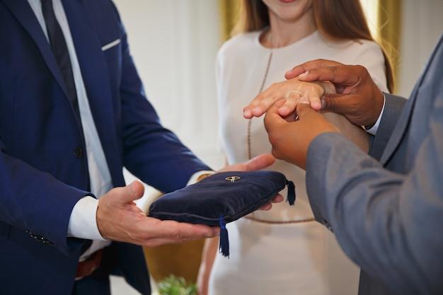 Gemengd ras paar hand in hand en trouwringen uitwisselen