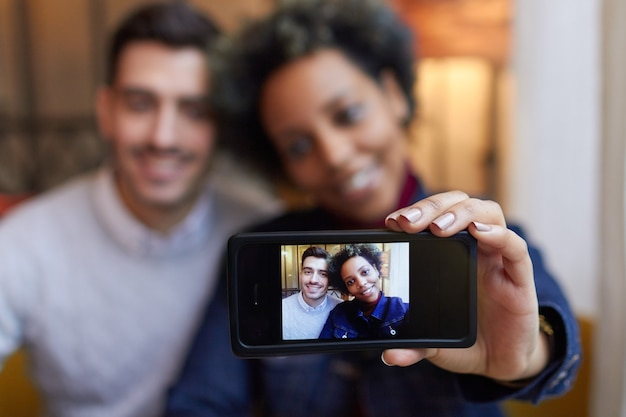 Gemengd ras paar selfie maken met telefoon in café