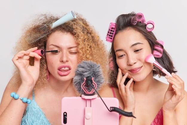 Gemengd ras professionele vrouwelijke vloggers maken schoonheidsproducten recensie record video blog via smartphone geven nuttige tips aan abonnees filmproces van het aanbrengen van mascara en gezichtspoeder doen kapsel