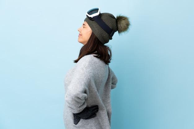 Gemengd ras skiër meisje met snowboard bril over geïsoleerde blauw lijden aan rugpijn voor een inspanning