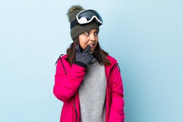 Gemengd ras skiër meisje met snowboard bril over geïsoleerde blauw nerveus en bang