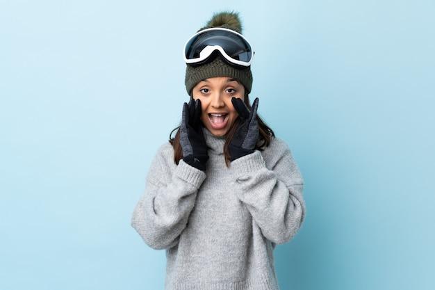 Gemengd ras skiër meisje met snowboard bril over geïsoleerde blauw schreeuwen en iets aankondigen