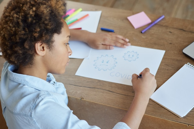 Gemengd ras tiener schoolmeisje covid tekenen op papier met kleurrijke markeringen terwijl ze tijd thuis doorbrengen
