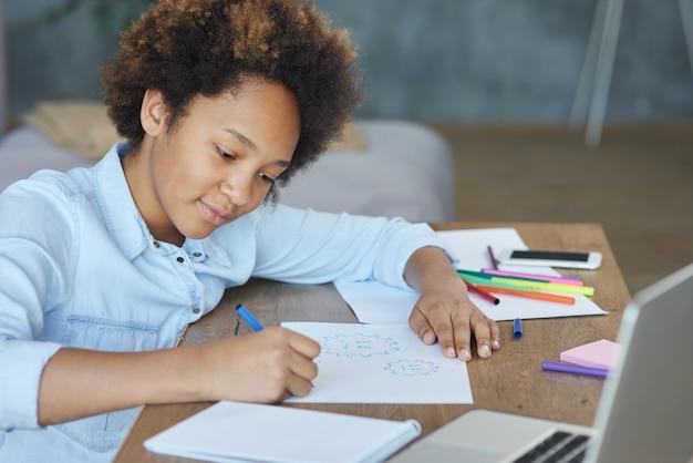 Gemengd ras tiener schoolmeisje op zoek gefocust tijdens het tekenen op papier met kleurrijke markeringen uitgaven