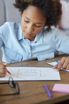 Gemengd ras tiener schoolmeisje tekenen op papier met kleurrijke markeringen terwijl ze tijd thuis doorbrengen