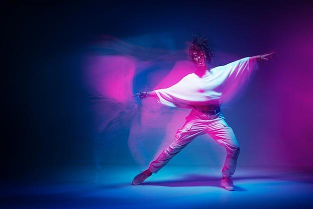 Gemengd ras vrouw dansen in kleurrijke neonlicht studio foto met lange blootstelling expressief