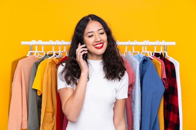 Gemengd ras vrouw in een kledingwinkel en praten met mobiel