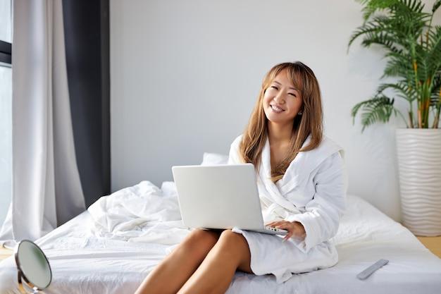 Gemengd ras vrouw zittend op breed wit bed met behulp van moderne laptop, praten met iemand online