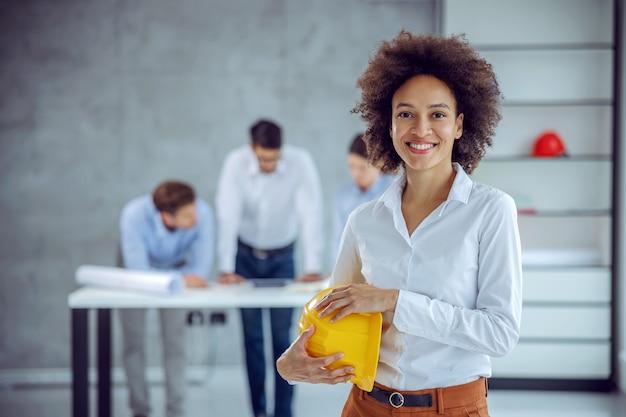 Gemengd ras vrouwelijke architect permanent in kantoor en helm in haar handen te houden