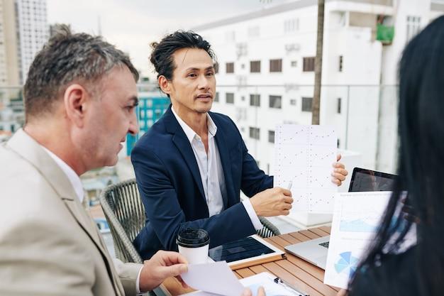 Gemengd ras zakenman wijzend op de grafiek in zijn handen wanneer hij met zijn collega's praat tijdens de vergadering
