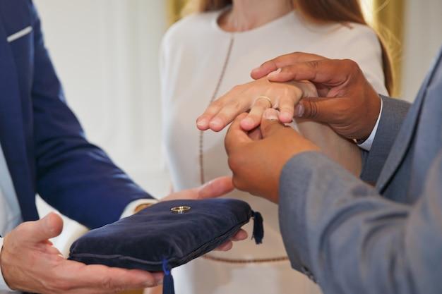 Gemengd ras zwart-wit interracial paar hand in hand en wisselen geloften en trouwringen uit tijdens de huwelijksceremonie. multiraciale familie