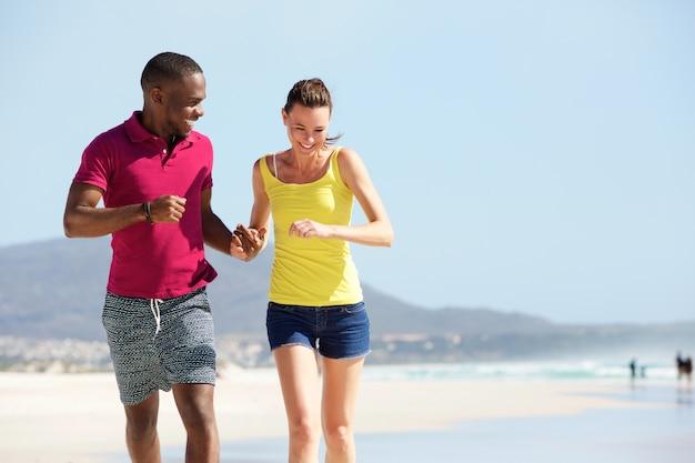 Gemengd raspaar die op het strand lopen