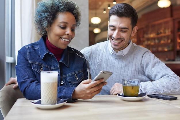Gemengd raspaar zit in café en deelt muziek die ze samen luisteren via de telefoon