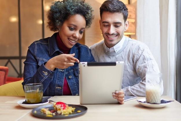 Gemengd raspaar zit in café en gebruikt de bank-app op de tablet