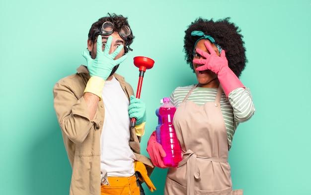 Gemengd stel dat geschokt, bang of doodsbang kijkt, het gezicht bedekt met de hand en tussen de vingers gluurt. huishoudelijk concept .. huisreparaties concept