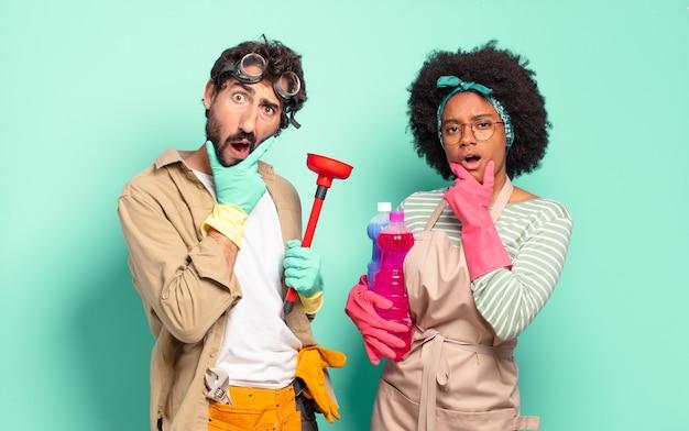 Gemengd stel met mond en ogen wijd open en hand op kin die zich onaangenaam geschokt voelen en zeggen wat of wauw huishoudelijk concept huisreparaties concept