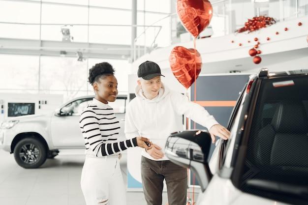 Gemengd stel. opname van een internationaal koppel shooses een auto. afrikaanse vrouw met blanke man.
