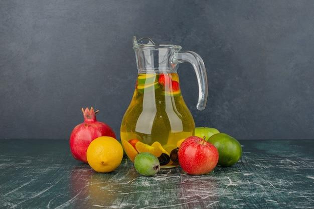 Gemengd vers fruit en een glas sap op marmeren tafel.