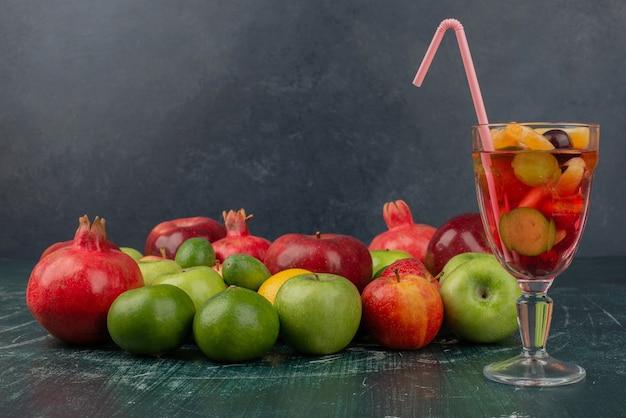 Gemengd vers fruit en glas sap op marmeren tafel