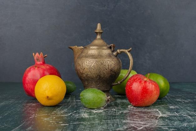 Gemengd vers fruit en klassieke theepot op marmeren tafel.