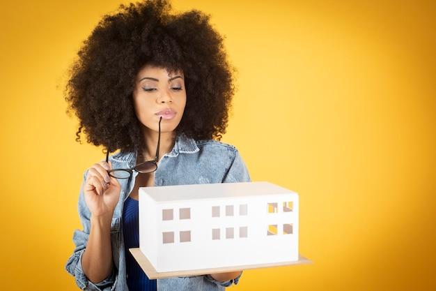 Gemengde afro-amerikaanse vrouw, afrohaar, mooie vrouw in denimkleren, op oranje achtergrond