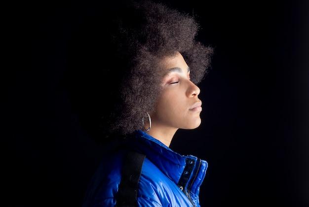 Gemengde afro vrouw die zich voordeed op een donkere achtergrond stedelijke kleding hip hop muziekstudio opname