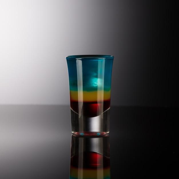 Gemengde alcoholische drank in een borrelglas geïsoleerd op een donkere achtergrond met achtergrondverlichting