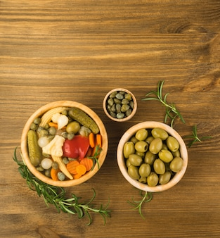 Gemengde augurken in houten kommen bovenaanzicht. gemarineerde komkommer, wortel, perl ui, baby maïs, paprika of rode peper, bloemkool, olijven en kappertjes