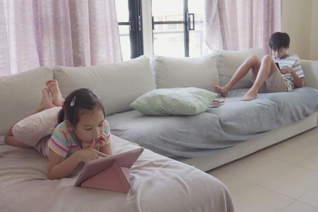 Gemengde aziatische kinderen die thuis digitale tablet gebruiken, luisteren naar podcast, gamen, online leeronderwijs, e-learning, thuisonderwijs, sociale afstand, isolatie, lockdown-concept