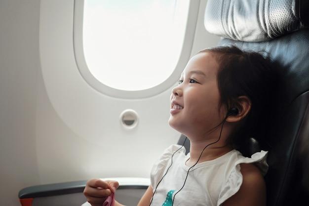 Gemengde aziatische meisje het letten op film tijdens de vlucht, familie die in het buitenland met kinderen reist