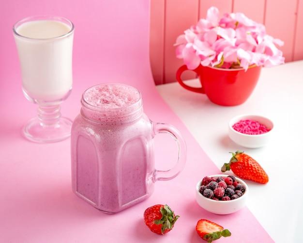 Gemengde bessenmilkshake met roommelk, aardbei, bevroren rode en zwarte bes op tafel